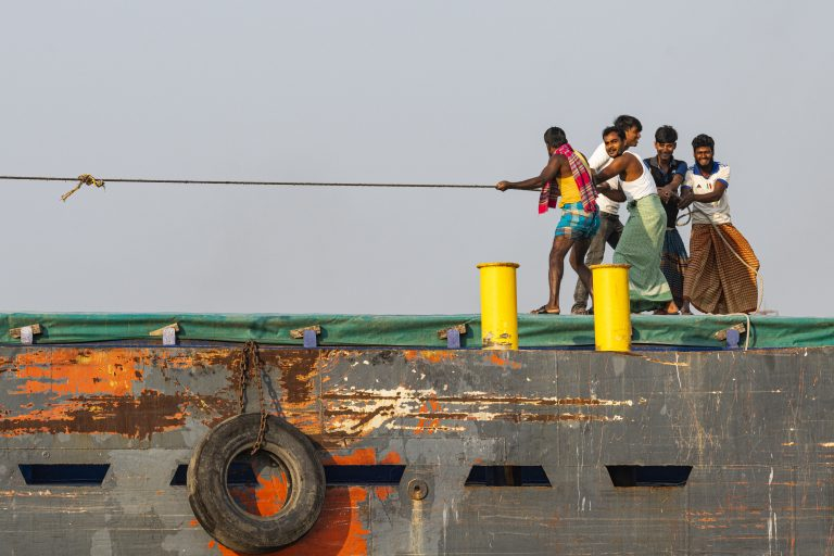 Travel Bangladesh,Men pulling a huge rope on a cargo boat